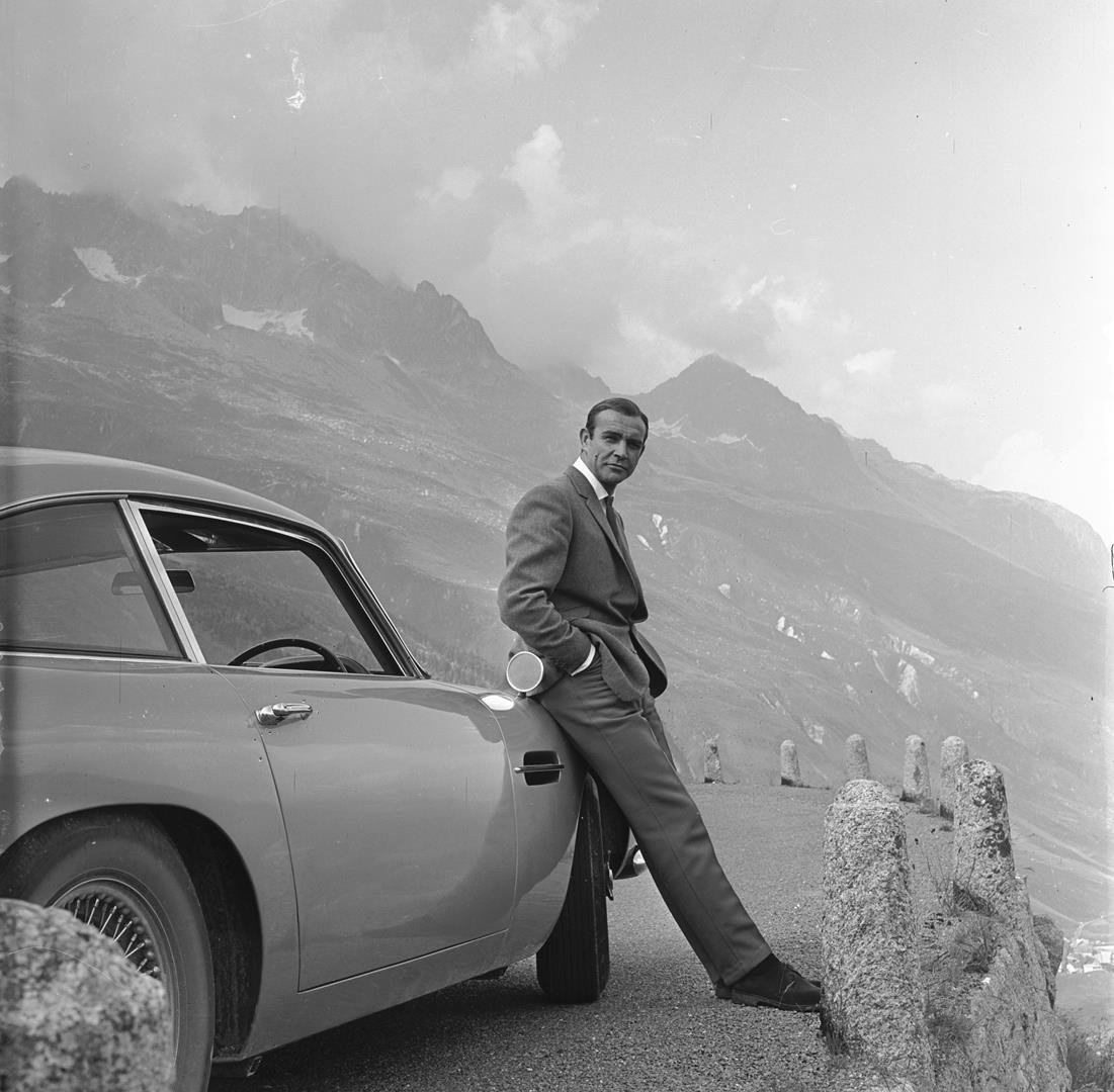 1. SEAN CONNERY relaxes on the bumper of his Aston Martin DB5 © 1964 Danjaq, LLC and United Artists Corporation. - LR.jpg